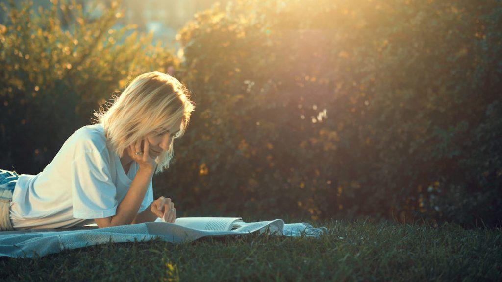 kobieta czytająca książkę na łące