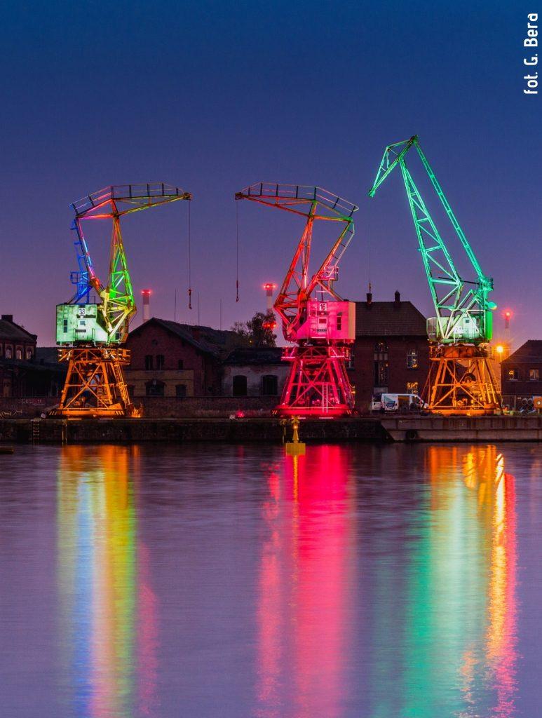 Zdjęcie wykonane przez Grzegorza Berę. Przedstawia trzy podświetlone na kolorowo dźwigi-żurawie stoczniowe na szczecińskiej Łasztowni, przed nimi widok na rzekę Odrę.