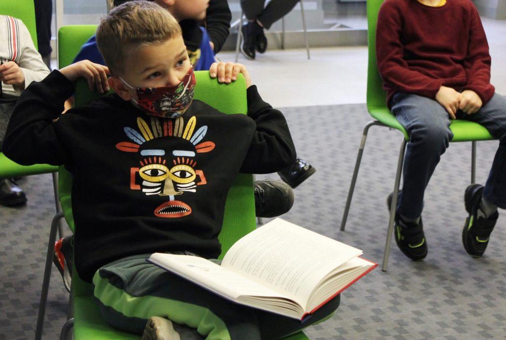 Dziecko podczas spotkania z otwartą książką na kolanach