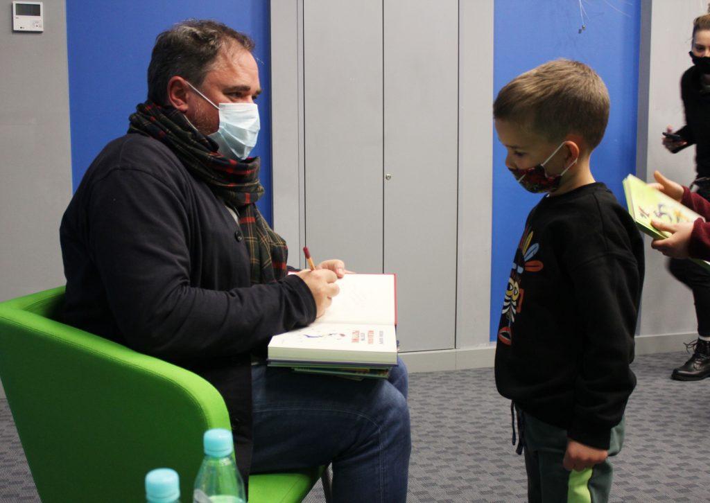 Chłopiec bierze autograf od autora