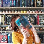 dziewczyna z książką na tle biblioteczki