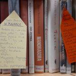 ksiązki na półce, przy dwóch książkach karteczki z opisem