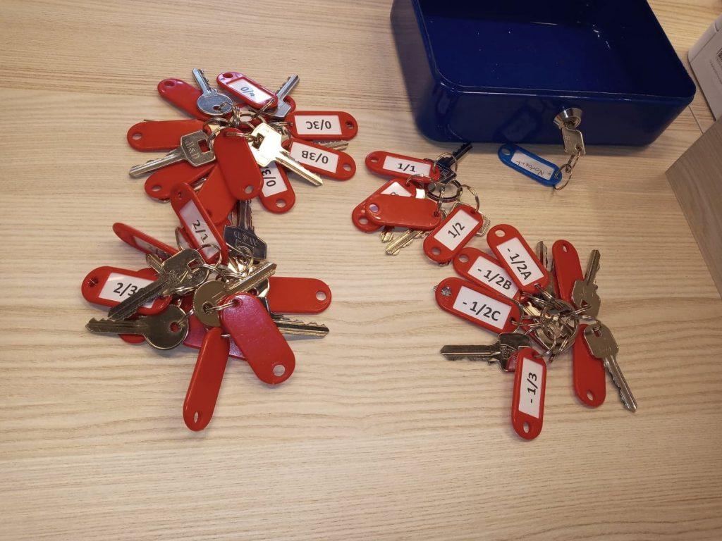 pęki kluczy z breloczkami leżące na blacie