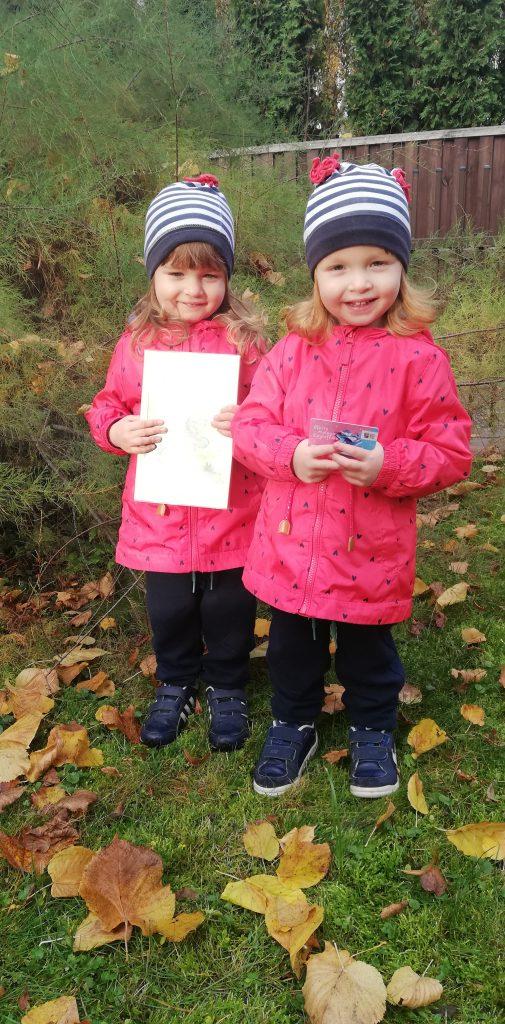 Dwie uśmiechnięte małe dziewczynki. Jedna z nich trzyma dyplom małego czytelnika, druga kartę do zbierania naklejek.