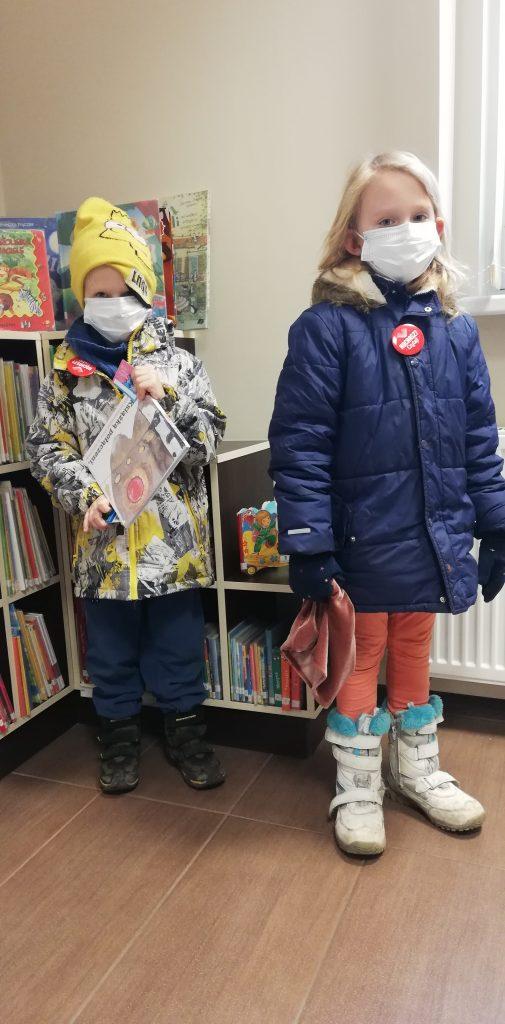 Chłopiec i dziewczynka w maseczkach na twarzy, stoją przed regałem z książkami w bibliotece. Chłopiec trzyma książkę dla dzieci.
