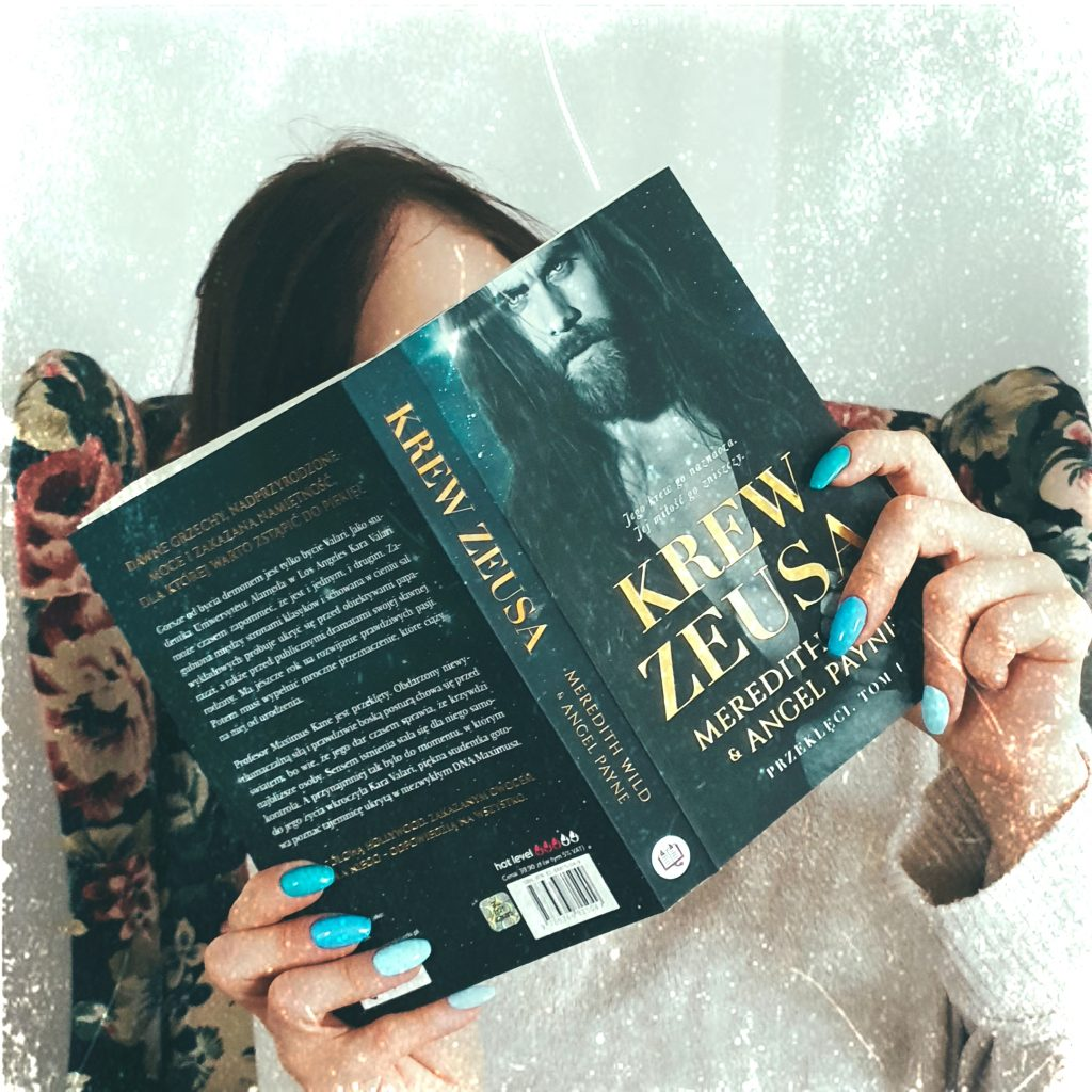 """dziewczyna zasłania się książką """"Krew Zeusa"""""""