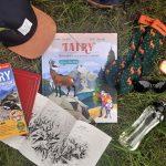 """Książka """"Tatry: przewodnik dla dużych i małych"""" leży na trawie. Obok niej butelka z wodą, czapka z daszkiem, skarpety, okulary przeciwsłoneczne i przewodniki po Tatrach"""