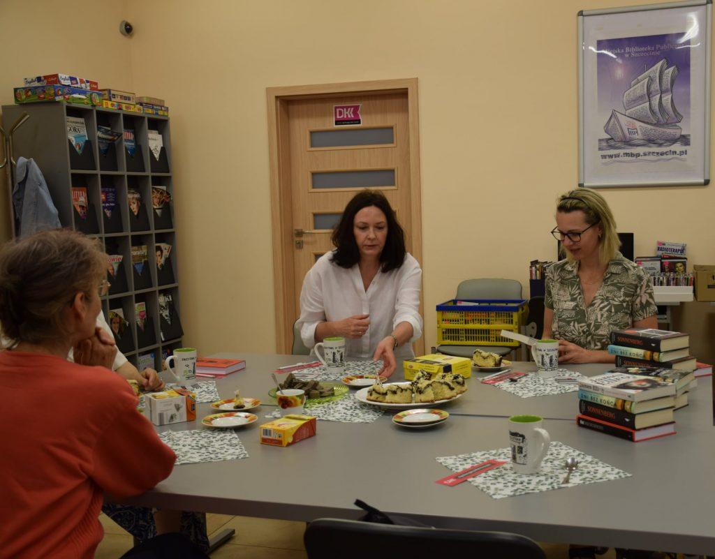 Uczestnicy spotkania DKK siedzą przy nakrytym stole, z zadowoleniem rozmawiają o książkach